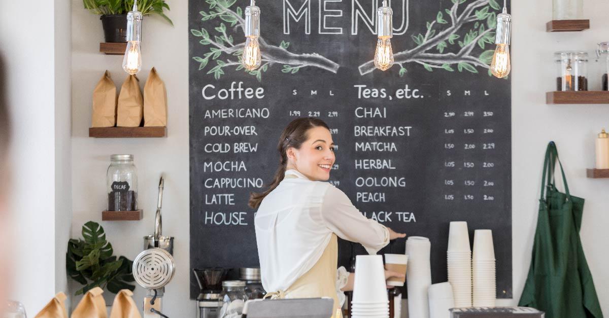 Restaurant worker at coffee and tea menu board